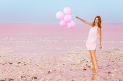 Beautiful woman with baloons on pink salt lake royalty free stock image