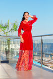 A beautiful woman posing on a blue sky background. A confident girl in a red dress smiling. A brunette lady on a hotel stock images