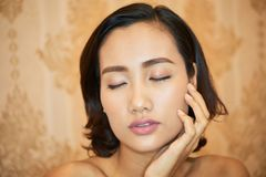 Beautiful Woman Posing fro Photography. Head and shoulders portrait of attractive Vietnamese woman posing for photography with closed eyes against peach stock photo