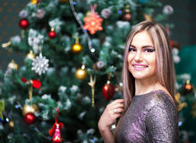 Beautiful woman posing in front of christmass tree Stock Photos