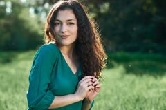Beautiful woman posing on green grass at sunny day, summer forest, bright landscape with shadows royalty free stock photos