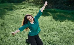 Beautiful woman posing on green grass at sunny day, summer forest, bright landscape with shadows stock photography