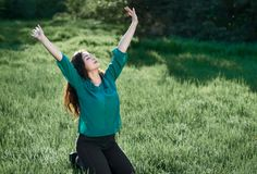 Beautiful woman posing on green grass at sunny day, summer forest, bright landscape with shadows stock photos