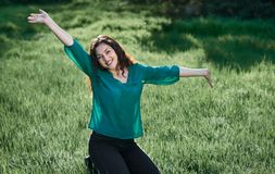 Beautiful woman posing on green grass at sunny day, summer forest, bright landscape with shadows royalty free stock images