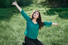 Beautiful woman posing on green grass at sunny day, summer forest, bright landscape with shadows royalty free stock photo