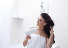 Beautiful woman posing with hairdryer in bathroom Royalty Free Stock Images