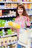 Beautiful woman posing with item. At supermarket royalty free stock images