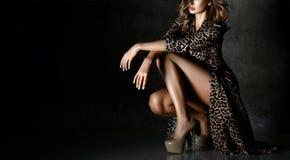 Beautiful woman posing in Leopard print dress on dark. Background royalty free stock photos