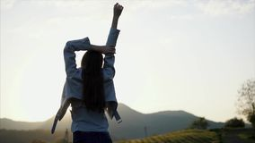 Beautiful woman posing in nature. Shot from behind of a fantastic girl in a fashionable clothes posing on a meadow in mountains during sunset. Nice walk on stock video footage