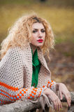 Beautiful woman posing in park during autumn season. Blonde girl wearing green blouse and big shawl posing outdoor. Long fair hair Royalty Free Stock Photo
