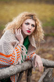 Beautiful woman posing in park during autumn season. Blonde girl wearing green blouse and big shawl posing outdoor. Long fair hair Stock Images
