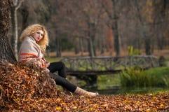 Beautiful woman posing in park during autumn season. Blonde girl wearing green blouse and big shawl posing outdoor. Long fair hair Royalty Free Stock Photo