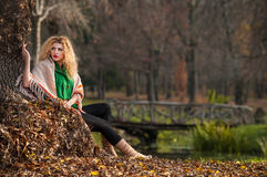 Beautiful woman posing in park during autumn season. Blonde girl wearing green blouse and big shawl posing outdoor. Long fair hair Stock Photo