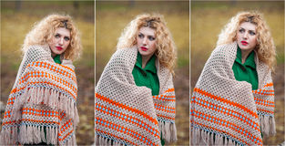 Beautiful woman posing in park during autumn season. Blonde girl wearing green blouse and big shawl posing outdoor. Long fair hair Royalty Free Stock Image