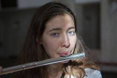 A beautiful woman posing while playing on a flute royalty free stock photos