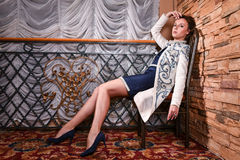 Beautiful woman posing pretty in the interior wearing designers coat. Beautiful woman posing pretty wearing designers white coat Stock Photo