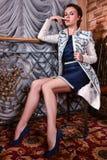 Beautiful woman posing pretty in the interior wearing designers coat. Beautiful woman posing pretty wearing designers white coat Stock Image