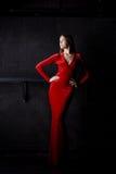 Beautiful woman posing in red long dress Stock Image