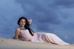 Beautiful woman posing on a sand dune Stock Photos