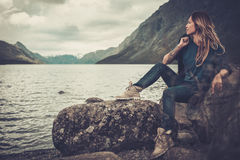 Beautiful woman posing on the shore of a wild lake, with mountains on the background. Stock Photo