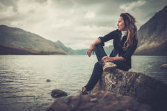 Beautiful woman posing on the shore of a wild lake, with mountains on the background. Confident woman posing on the shore of a wild lake, with mountains on the Stock Images