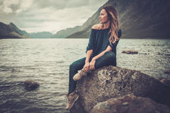 Beautiful woman posing on the shore of a wild lake, with mountains on the background. Confident woman posing on the shore of a wild lake, with mountains on the Stock Image