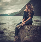 Beautiful woman posing on the shore of a wild lake, with mountains on the background. Royalty Free Stock Image