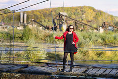 Beautiful woman posing on the suspension bridge on a autumn sunny bright day. Beautiful blond woman posing on the suspension bridge on a autumn sunny bright day Stock Image