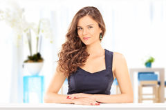 Beautiful woman posing at a table indoors Stock Images
