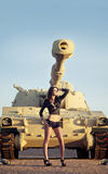 Beautiful woman posing beside tank Stock Image
