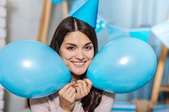 Beautiful woman posing with two balloons near her cheeks Stock Image