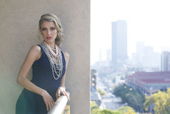 Beautiful woman posing on urban balcony with city view Stock Images