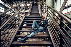 Beautiful woman posing wearing casual outfit with leather jacket, black shoes and fashionable jeans. Girl posing in industrial pla. Nt royalty free stock photos