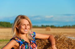 Beautiful woman   posing on a wheat bale Royalty Free Stock Photography