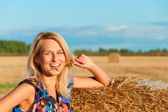 Beautiful woman   posing on a wheat bale Royalty Free Stock Image