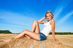 Beautiful woman posing on a wheat bale in a field Stock Images