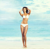 A beautiful woman posing in a white swimsuit on the beach Royalty Free Stock Photo