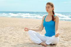 Beautiful woman practice yoga on the beach Stock Image