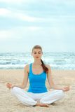 Beautiful woman practice yoga on the beach Stock Photos