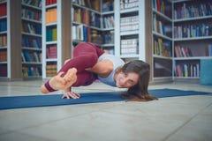 Beautiful woman practices handstand yoga asana Ashtavakrasana pose in the library stock photo