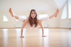 Beautiful woman practices handstand yoga asana Tittibhasana - firefly pose in the yoga studio.  Royalty Free Stock Photo
