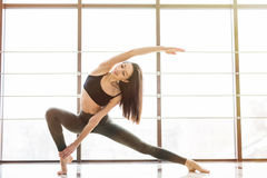 Beautiful woman practices yoga asana Anjaneyasana in studio royalty free stock photos