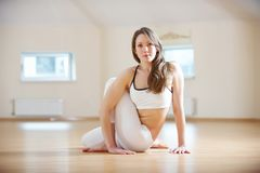 Beautiful woman practices yoga asana Ardha Matsyendrasana - Half spinal twist pose in the yoga studio.  Royalty Free Stock Photo