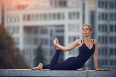 Beautiful woman practices yoga asana Ardha Bhekasana - Half Frog pose outdoors against the background of a modern city. Beautiful woman practices yoga asana stock photos