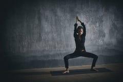 Beautiful woman practices yoga asana Stupasana in the dark hall Royalty Free Stock Images