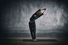 Beautiful woman practices yoga asana Tiriaka Tadasana in the dark hall Stock Photo