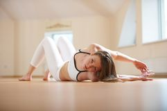 Beautiful woman practices yoga lying twisted asana in the yoga studio Stock Image