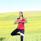 Beautiful woman practices yoga. In nature against the yellow field Royalty Free Stock Photo