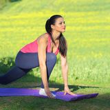 Beautiful woman practices yoga. In nature against the yellow field Royalty Free Stock Photography
