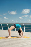 Beautiful woman practices yoga on sea Stock Photo